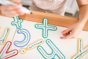 Learn & Grow Toys Write and Wipe lowercase letters being used by a child on a desk for educational play