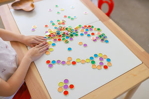 Metal Rimmed Counting Chips for counting, sensory and creative play displayed across white desk with child playing