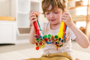 Child playing with magnetic wands and counting chips used for sensory play and counting games