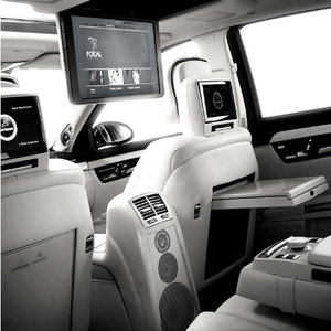 Interior shot of a luxury vehicle with white leather interior featuring screens in the headrests, a screen mounted on the front dash, and speakers on the back of the arm rest.