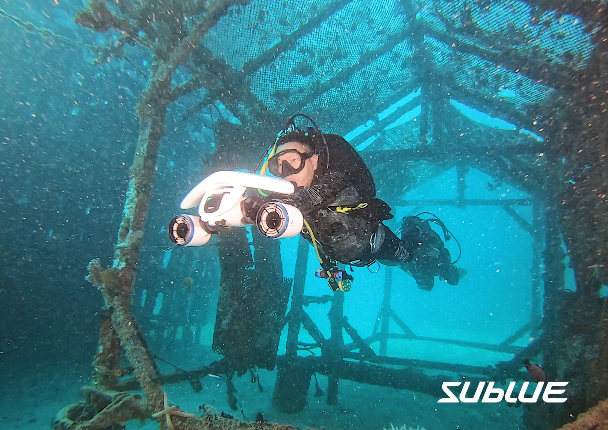 Picture of scuba divers under water in a cage swimming with a Sublue self-propelled handheld scooter.