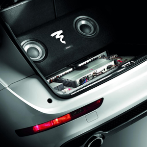Rear of a silver car with the trunk open featuring a custom audio system with a pair of speakers and a sub-woofer with the Focal logo.