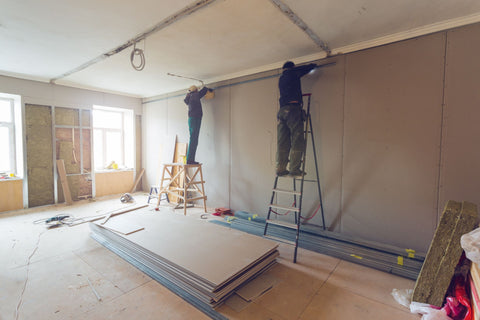 Workers are installing plasterboard for gypsum walls