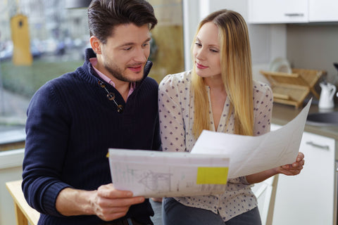 Young couple standing in a kitchen holding blueprints of a new design or renovation