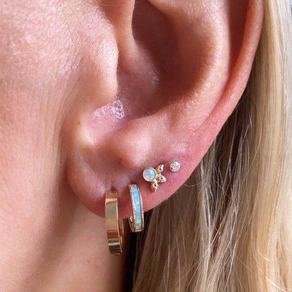 In the first hole is our classic cool girl hoops, followed by the gold & opal inlay hoops. In the third hole are the Beatrix Australian opal studs and finally the stardust stud. These earrings make the perfect stack, a dream ear if you will.