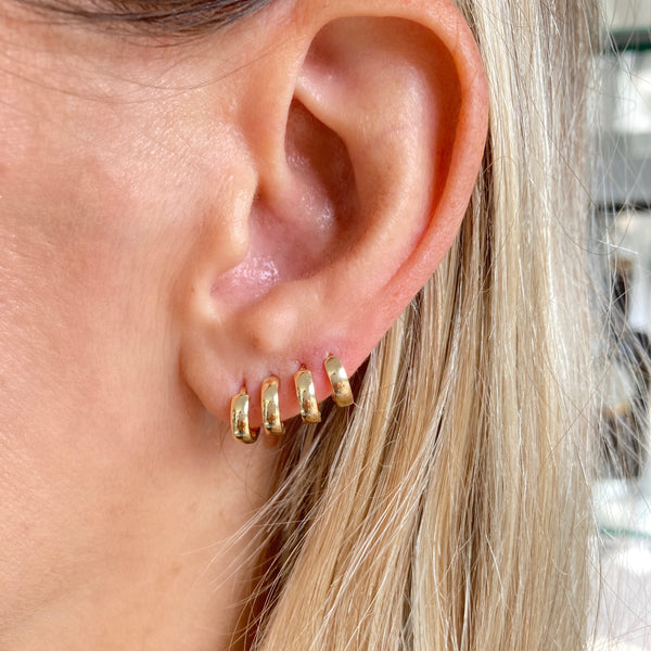 Four 14k gold tiniest biggie hoops. Our classic Huggie made for stacking or worn alone.