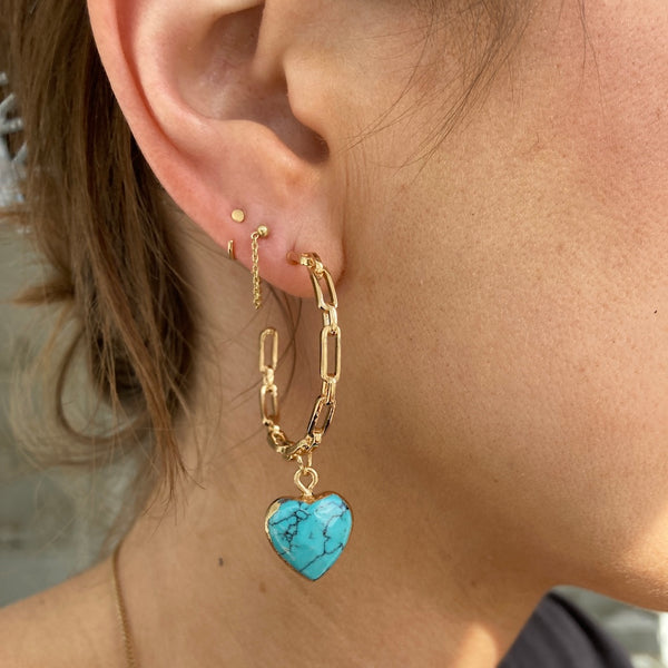 The turquoise heart hoops are paired with out chained forever earrings and our tiniest huggie hoops.