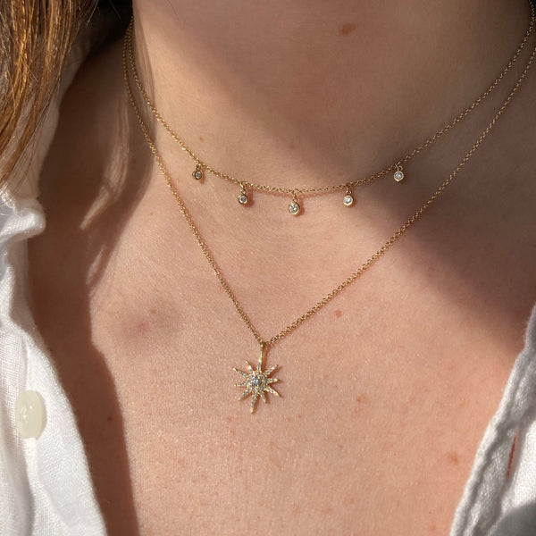 The yellow gold dew drop diamond station necklace is paired with our starburst diamond necklace.