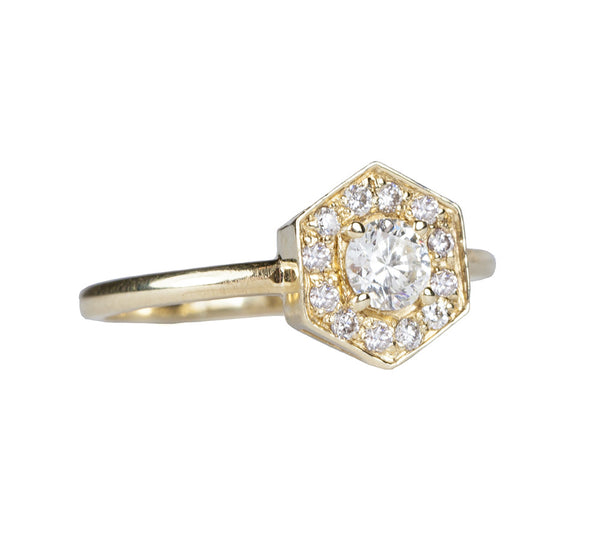 Katie Diamond's Lila Ring is an engagement ring with a round center stone and hexagon shaped diamond halo.