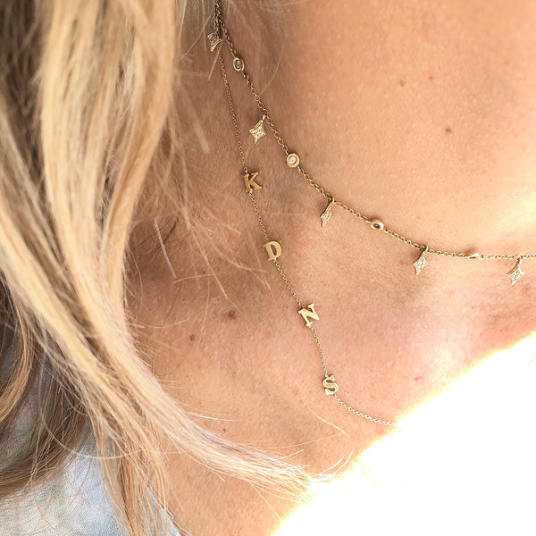 layered gold station and initial necklaces