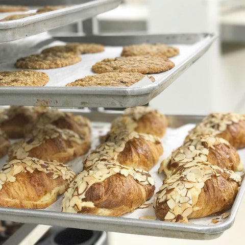 Freshly baked almond croissants and cookies on oven racks