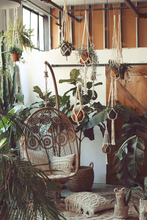 "Load image into Gallery viewer, 24"" Beaded Plant Hanger displayed in boho room with swing chair, pillows and lots of plants!"