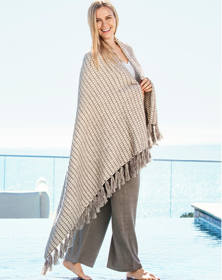 Channel beach house vibes wherever you reside with this light yet cozy blanket, which features chic tassles, a subtle knitted grid pattern and soothing colors.