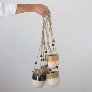 "hand holding 4 ceramic hanging planters that hold 4"" pots"