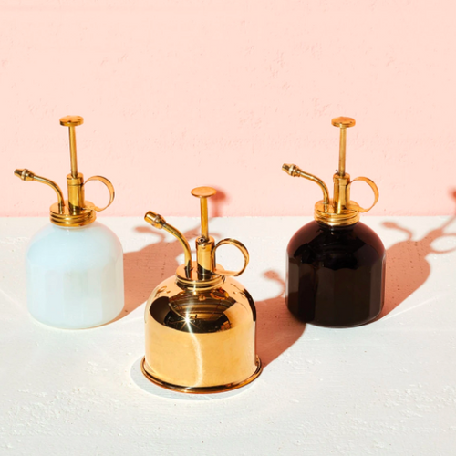 3 misters, a brass, a white glass with brass top, a black glass with copper top