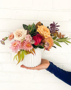 Person holding a colorful + Unique arrangement of flowers