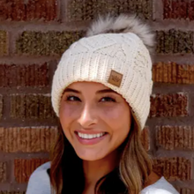 Load image into Gallery viewer, Topped with a pom, this fleece lined cream cable knit beanie keeps you warm and cozy all season long.