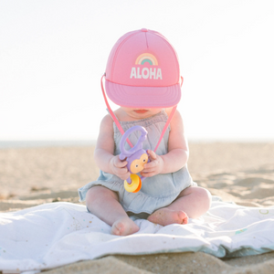 Aloha Rainbow Trucker Sun Hat on baby girl with rattle on beach