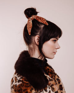 The Hendrix Gold Velvet Scrunchie Tie in woman with leopard coat