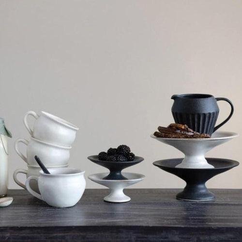 Matte Stoneware Pedestals alongside assorted black and white pottery