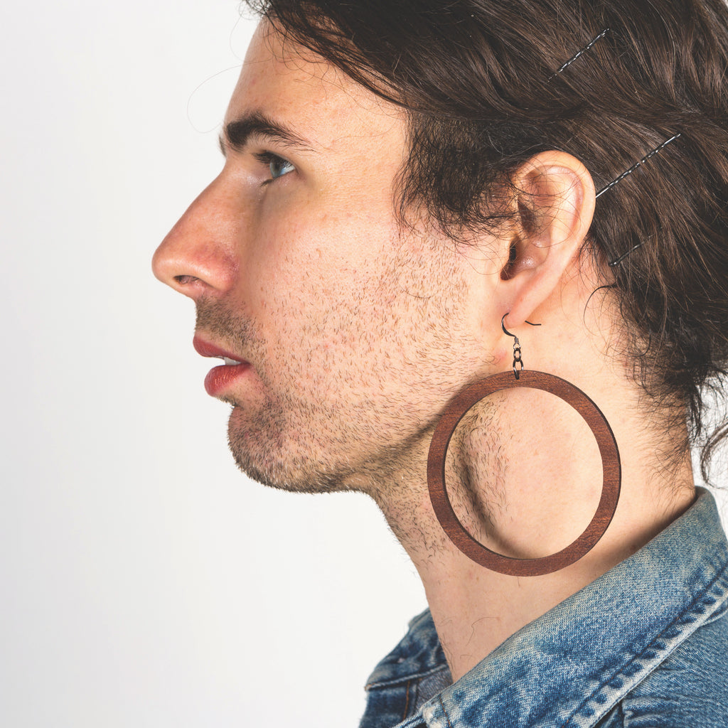 Model wearing grand sized laser cut wood earrings from Create Laser Arts