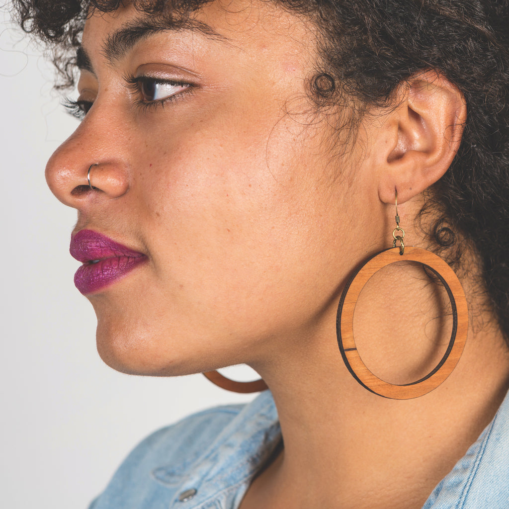 Model wearing large laser cut wood earrings from Create Laser Arts