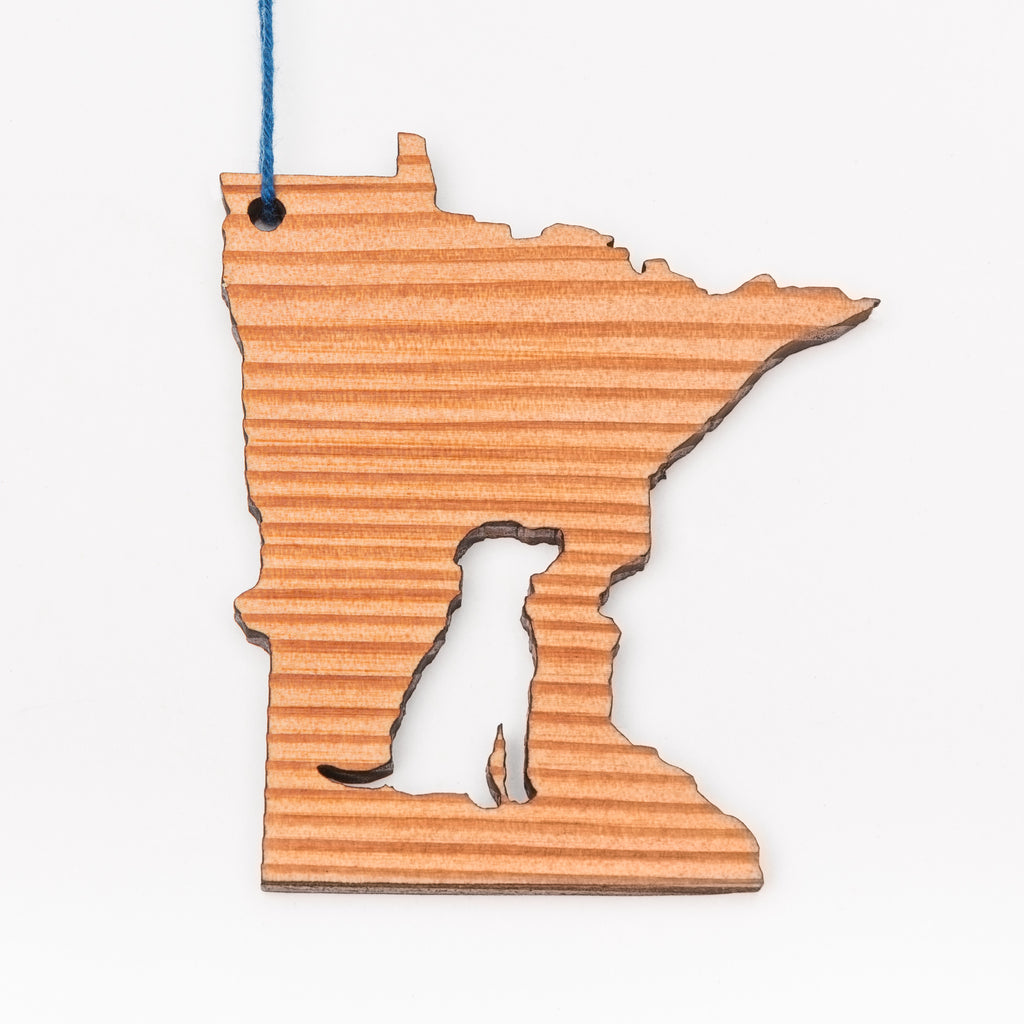 A wood ornament in the shape of Minnesota with the image of a dog cut out of the middle