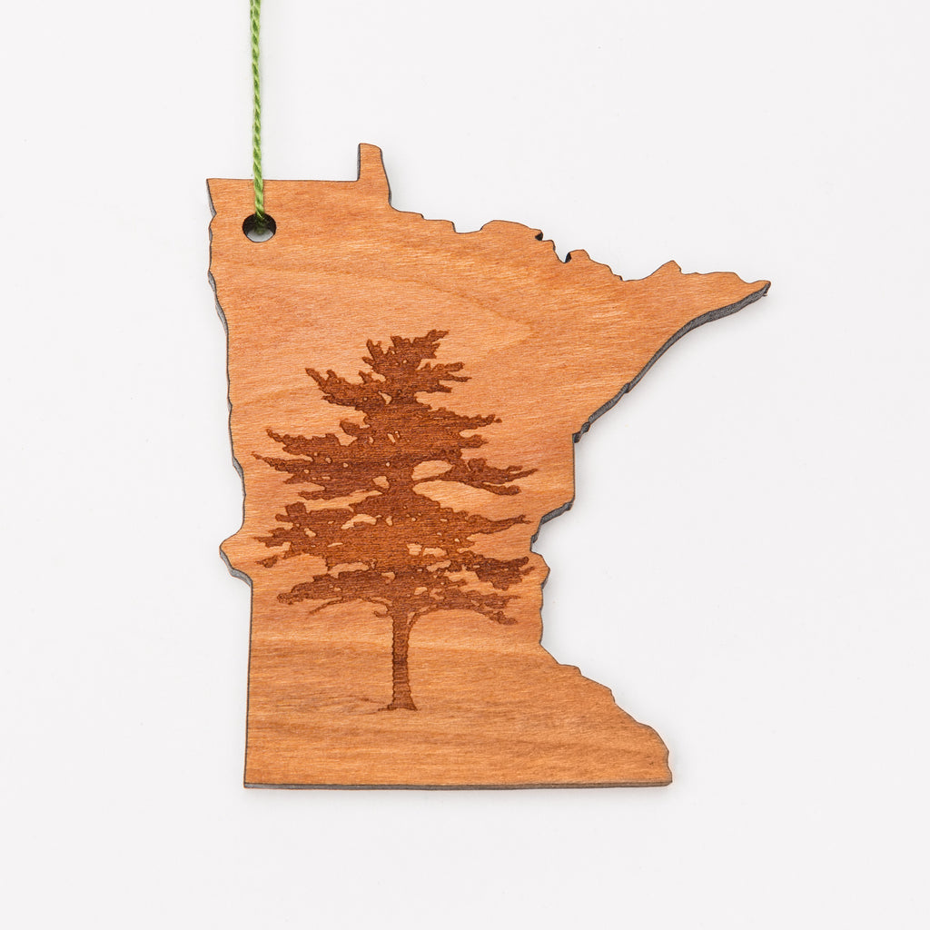 Pine tree laser etched into a Minnesota-shaped wood ornament