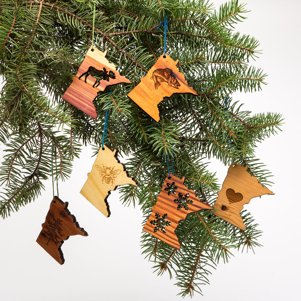 Laser cut wood minnesota-shaped ornaments hanging from a tree