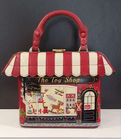 Vendula Toy Shop Grab bag is one of the original Grab bags that have the metal frame on the roof which gives these bags their very French shop look! Adorned with toys that are well stitched on and so much detail.   The grab bag range comes with a long strap, which can replace the handle strap, internal pocket and a structured frame for easy access.  Vendula bags are vegan approved, designed in London, and are limited editions, with collectors all over the world.
