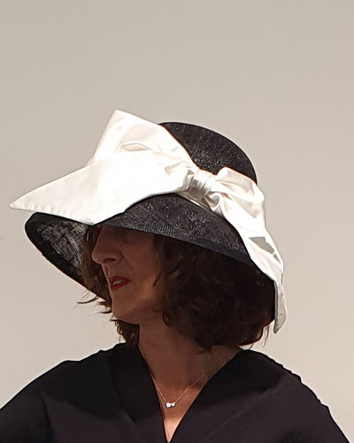 Fabulous Audrey hat is a classic wide and deep rimmed hat, with a large off white satin bow. Perfect for a wedding , races or any outdoor specials occasion. Made in London Only 1 Available