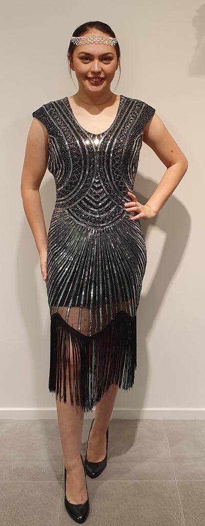 Black and Silver gatsby dress with fringe tassels, super for a 1920's party light and as some stretch. This is a comfortable ,sparkly , fun dress Available in Sml, Med, Lrg Sml 8-10 med 10 -12 Lrg 14-16