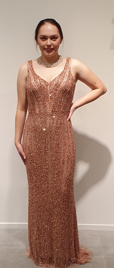 Stunning Rose gold fully sequined, fitting gown a must for any occassion where you want to make a statement! This gown offers ease of movement, and more sparkle than NY on New Years Eve. One Available size 12-14
