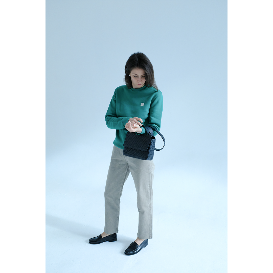 Woman wearing a green sweatshirt with chinos, leather loafers and a leather bag