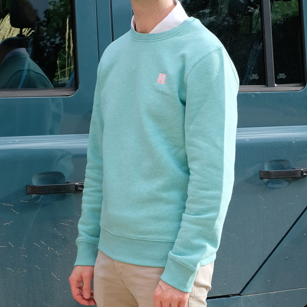 Man wearing seafoam green sweatshirt over a white shirt