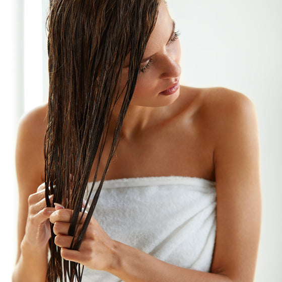 woman in towel applying leave-in silicone-free conditioner
