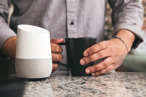 Man with Coffee and Google Home Assistant