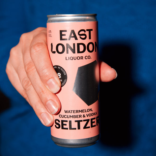 A can of East London Watermelon, Cucumber & Vodka seltzer in hand against an electric blue background.