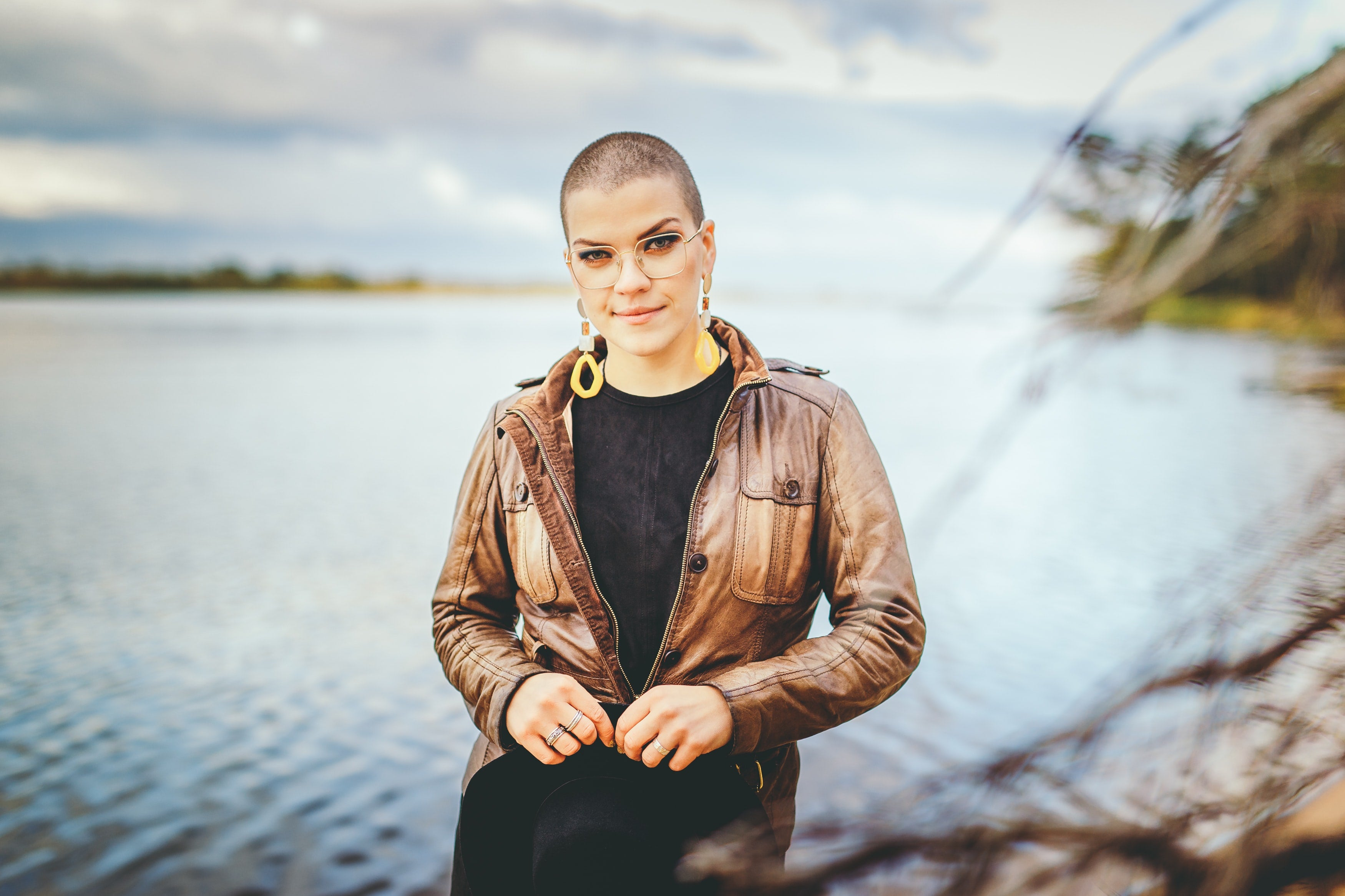 Woman with buzzcut in front of lake