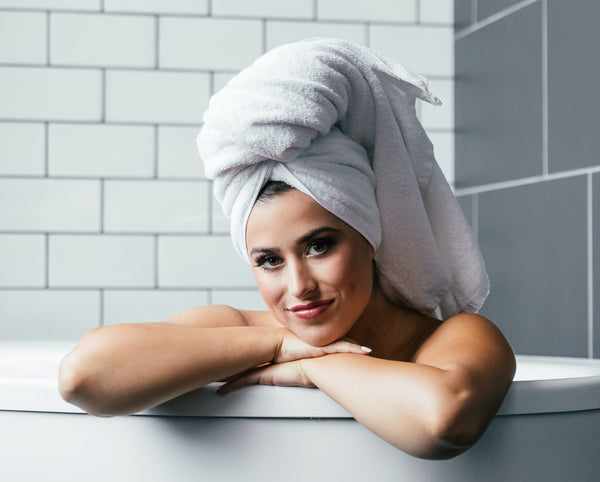 Woman in bathtub with hair wrapped in a cotton bath towel