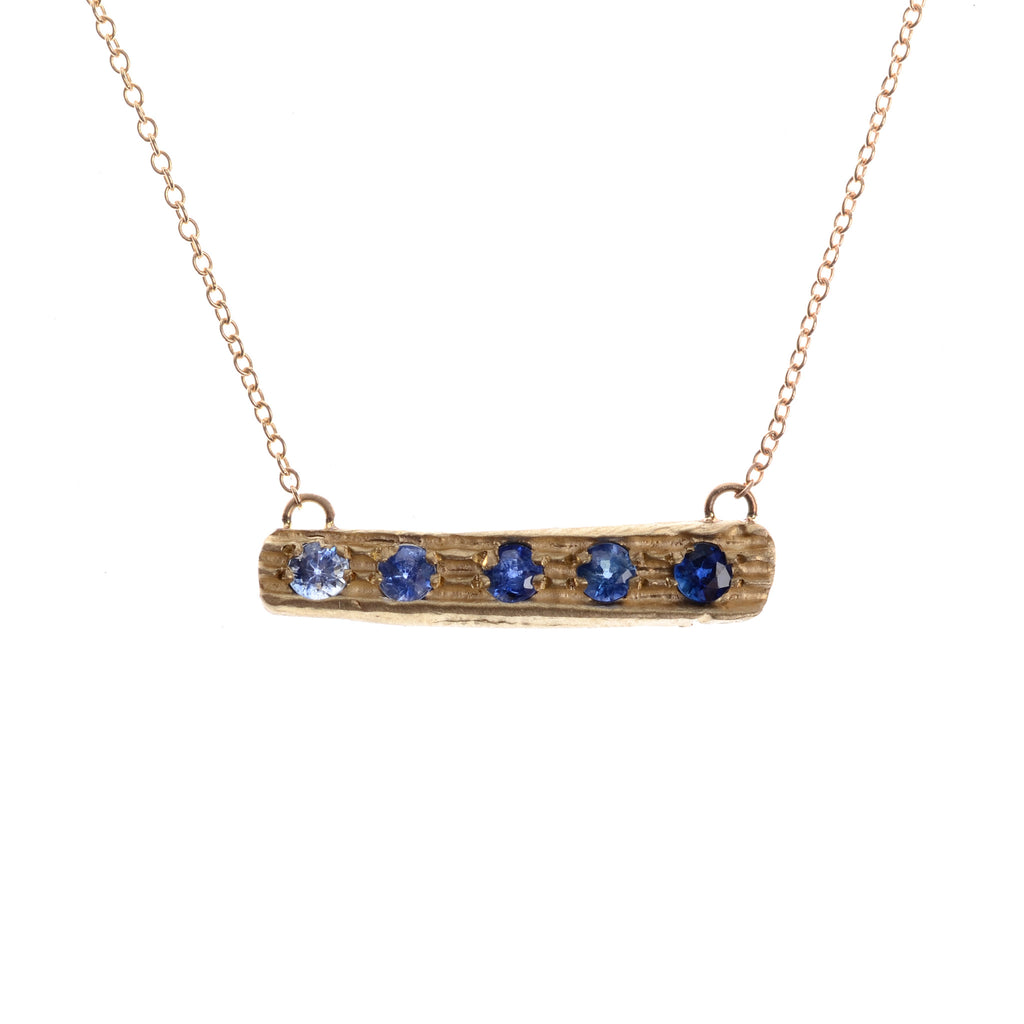 Horizontal bar with gradations of blue sapphires