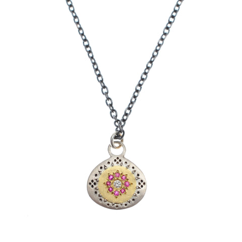 "Small disc pendant of sterling silver and 14kyg with inlaid rubies and diamonds on oxidized 16 "" chain"