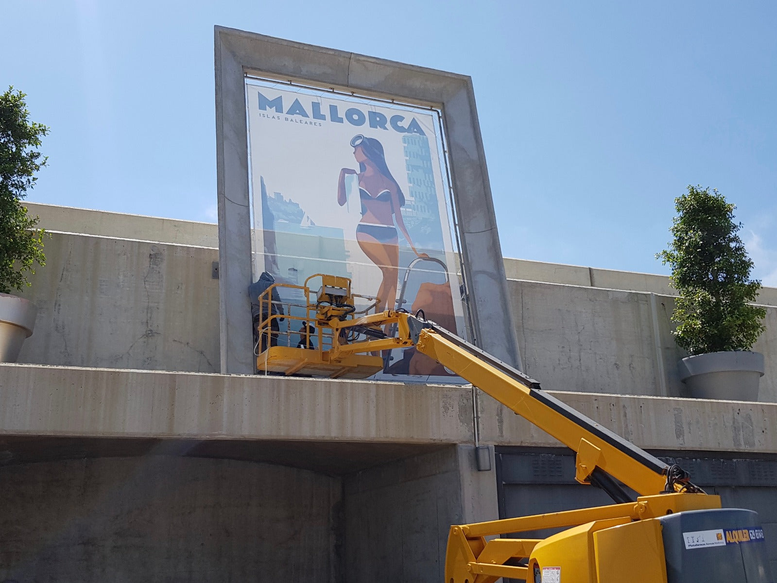 Crane putting up  industrial scale / giant version of La Nadadora poster on either an airtex type perforated material or flex as per this Philippe Starck-framed 5 x 3 metre example