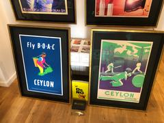 Two framed limited editions of Ceylon prints (BOAC and Bad Light Cricket) on a wooden table