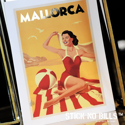 Foiled travel poster of a woman in a red swimsuit sitting on a beach towel, at Playa de Canyamel, Mallorca.