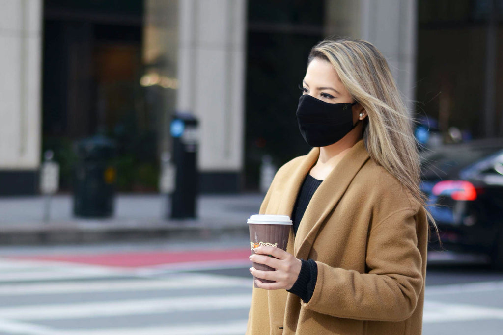 woman wearing a face mask and holding a coffee cup