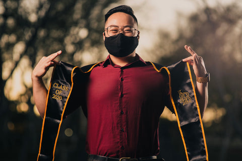 college graudate with black ora mask with sash