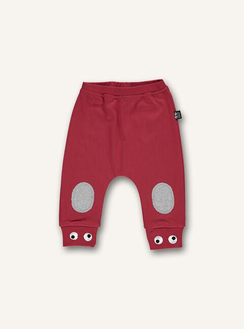 UBANG baby pants in red. They have an elasticated waist and eyes embroided at the bottom of the pantlegs.