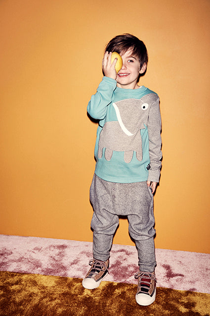 Boy wearing UBANG elephant t-shirt in porcelain and UBANG pants in grey.