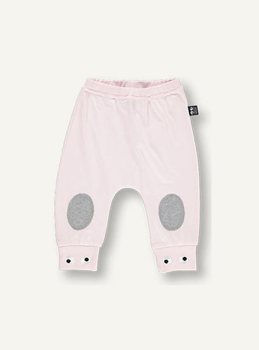 UBANG baby pants in light blush pink. They have grey padding on the knees and embroidered eyes on the bottom of the legs.